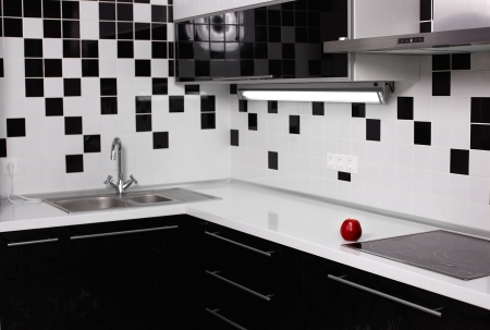 interior of black and white modern kitchen with red tasty apple photo