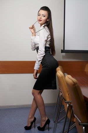 portrait of young sexy business woman in an office with glasses red lips photo