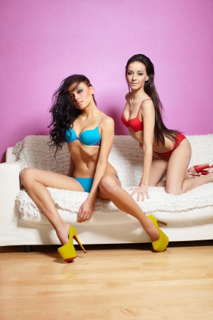 female pose: two beautiful sexy brunette modesl women in red and blue lingerie posing on white sofa  pink wall in  open-toes