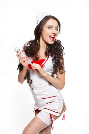 Sexy beautiful smiling female brunette doctor with big syringe red lingerie white stocking and red lips on a white background long curly hair Stock Photo