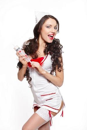 doctor verpleegster: Sexy mooie glimlachende vrouwelijke brunette arts met grote spuit rode lingerie witte kous en rode lippen op een witte achtergrond lang krullend haar Stockfoto