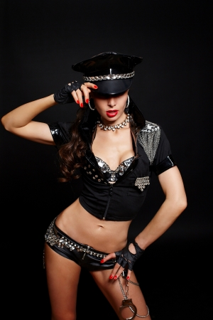 semi nude: sexy beautiful  brunette semi nude police woman with long curly hair with handcuffs  with birght makeup and red lips isolated on black