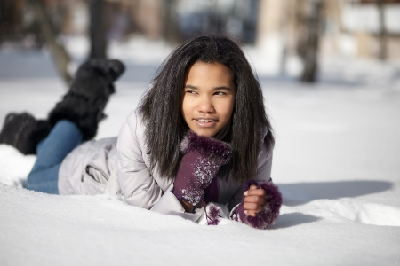 Beautiful smiling american black female lying in the snow outdoors photo