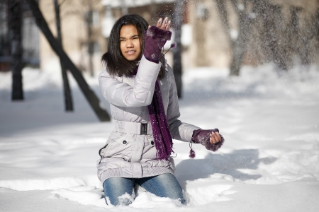 Beautiful smiling american black female sitting in the snow outdoors playing with snow photo