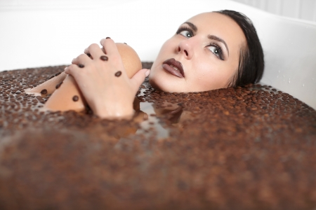 Portrait of beautiful fashion girl in jacuzzi with coffee. Body care. bright makeup Фото со стока