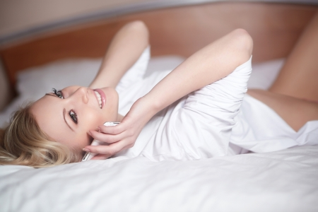 Young happy smiling beautiful girl lying on bed and speaking on phone photo