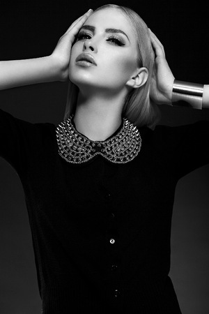 High fashion look.glamor closeup portrait of beautiful sexy stylish blond  young woman model with bright makeup  with perfect clean skin with  jewelery in black cloth Stock Photo