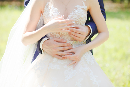 The bride and groom wear wedding rings to each other, simultaneously Stock Photo