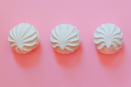 three white marshmallows lying on a pink background