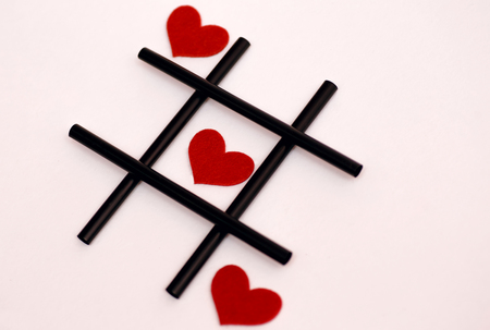 Valentines Day, February 14, tic-tac-toe concept, on a white background, black tubules for juice and red felt hearts Stok Fotoğraf