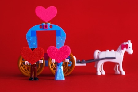 The 14th of February. Valentines Day. Toy carriage. Two toy little men hold red hearts on a red background