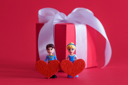 The 14th of February. Valentines Day. Two toy little men hold red hearts on the background of a gift