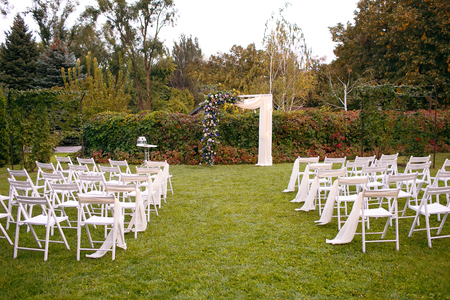 Wedding. Ceremony. Wedding arch. Wedding arch made of branches, flowers and greenery is on the green grass on the river bank. 스톡 콘텐츠