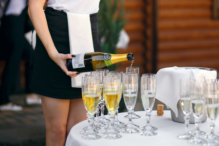 Waitress pouring champagne into glasses, celebration. party