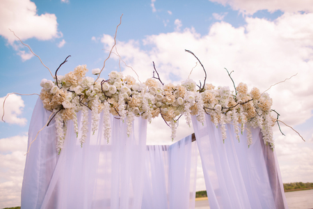 Wedding. Ceremony. Wedding arch. Wedding arch of branches, flowers and greenery stands on the green grass on the banks of the river against the sky