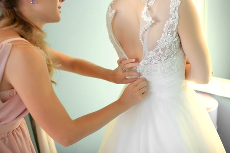 Bridesmaid helping slender bride lacing her wedding white dress, buttoning on delicate lace pattern with fluffy skirt on waist. Morning bridal preparation details newlyweds. Wedding day moments, wear.