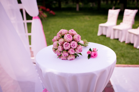 A beautiful wedding bouquet of peony roses, lies on a white table, everything is ready for the wedding ceremony, beautiful pink peonies