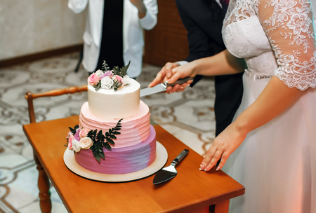 The bride and groom at the wedding cut the wedding cake, the cake is decorated with flowers. Imagens
