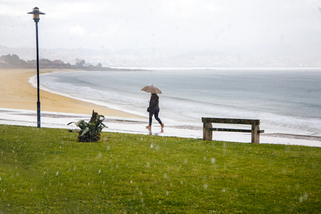 a woman with an umbrella is walking along the embankment, it is raining, the Atlantic Ocean, bad weather.