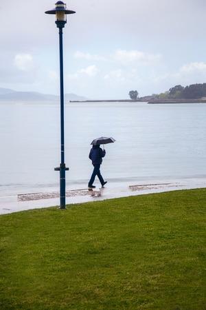 a man with an umbrella is walking along the embankment, it is raining, the Atlantic Ocean, bad weather. 版權商用圖片