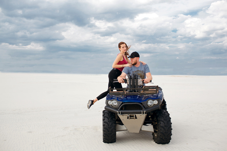 a girl climbs her boyfriend on a quad bike, they are preparing for a trip in the desert, a stylish young couple
