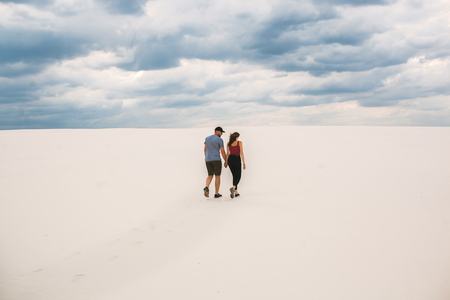 the girl and the guy are walking in the desert, the couple in love holds each others hands, but they are lost in the desert Reklamní fotografie