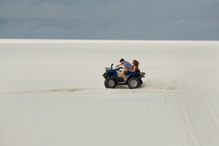 The guy and the girl ride a quad bike in the desert, having fun and enjoying, a couple of lovers