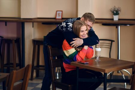 In the cafe, a man meets a woman, a guy hugs a girl, they are happy to see a friend of a friend, a young couple smiles and enjoys