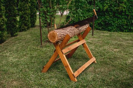Sawing logs on a wooden stand on a green lawn, hand saw, friendship