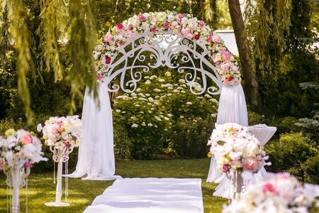 a beautiful wedding arch decorated with flowers in the forest, a white path is ready for the newlyweds