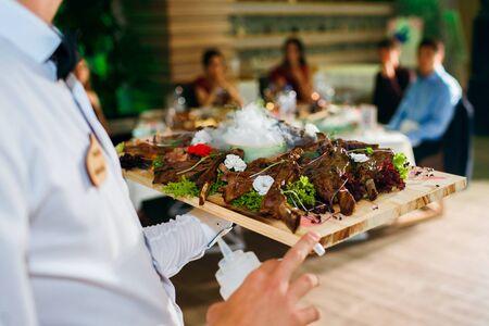Costillas de carne en una bandeja con nitrógeno líquido, el camarero entrega la comida en el fondo de los invitados, un plato delicioso Foto de archivo