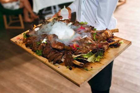 meat ribs on a tray with liquid nitrogen, the waiter delivers food in the background of the guests, a delicious dish