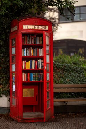 A red telephone booth on a London street, there are books in a telephone booth, books on the shelves of a telephone booth.