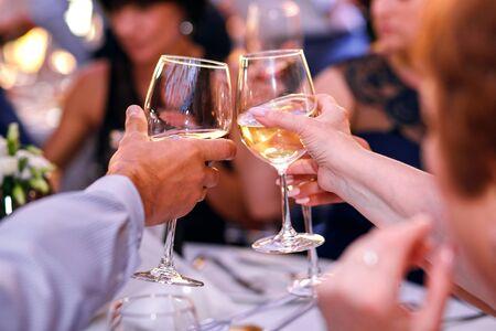 tintineo de copas en una fiesta, vino blanco y champán, diversión de una gran compañía Foto de archivo