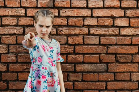Angry teenager girl on brick wall background