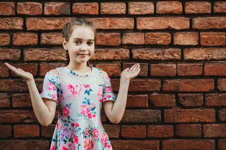 teenager girl spreads her arms to the side, emotion of surprise on a background of a brick wall