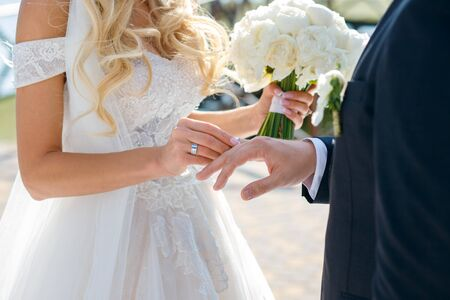 The bride puts a wedding ring on the groom finger, a beautiful wedding ceremony with fresh flowers, a beautiful girl and a courageous guy.