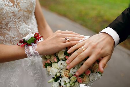 Hands of the newlyweds with rings on their fingers, near a bouquet of roses, the bride and groom hold hands, happy couple, future family