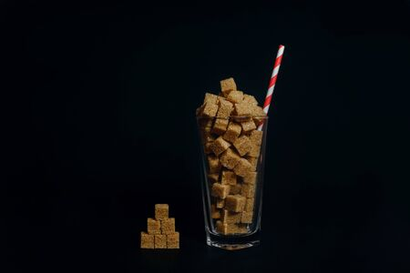 transparent glass cup with brown cane sugar cubes on a dark table on black background