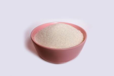 pink plate with sugar on a white background, flavoring or harmful substance, development of diabetes, white sugar top view Banco de Imagens