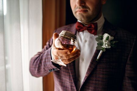 A man holds a glass with whiskey, dressed in a classic suit, a beautiful glass with cognac, a respectable man, male style, alcohol, a man stands near the window