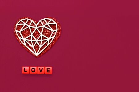 composition for february 14, love day, white heart on a red background, the inscription love from cubes, valentines day, place for text, beautiful love card
