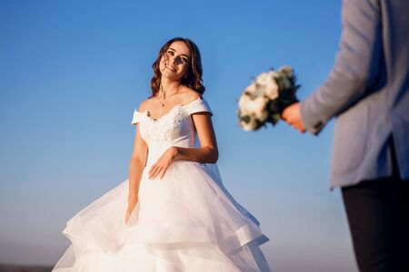 The bride and groom are standing near the river against the blue sky