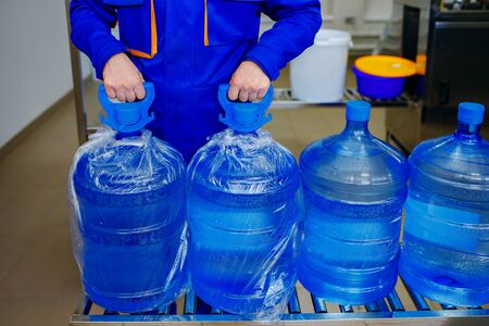 Pure water plant, male loader wears large bottles of clean drinking water, worker hands closeup, home water delivery, strong hands, work process 版權商用圖片
