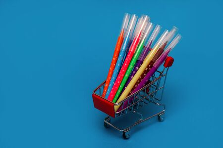 trolley with colorful felt-tip pens on blue background, objects for drawing, drawing for children, toy shopping trolley, side view Stockfoto