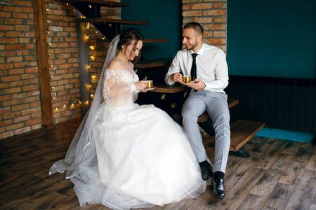The bride and groom are sitting in a cafe and drinking coffee, smiling and enjoying a tasty drink, a beautiful cozy interior with lamps and steps in the form of chairs, a long wedding dress