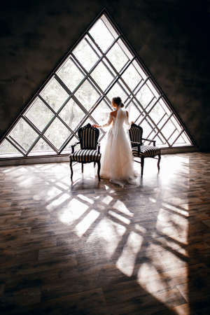 bride in a wedding dress near two striped armchairs, vertical photo, against the background of a triangular window, empty attic, stylish view, vintage interior, incredible window, beautiful design