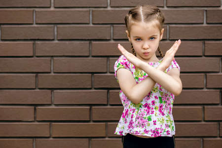 A little serious girl stands near a brick wall and shows enough or a stop sign with a gesture. A cute little girl with pigtails waves her hands emotionally and is very unhappy. Free space for text