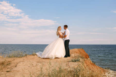 The bride and groom hug on the edge of the mountain against the background of the sea. An elegant bride in a white wedding dress looks lovingly at her husband. Happy newlyweds hugging