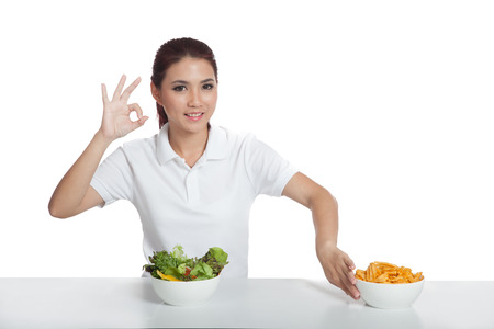 Asian girl push away potato chips and show OK hand sign for salad in front of her photo